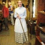 Docent in period costume in barn museum.