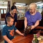 Shelton House educator shows clay jug to young visitor.