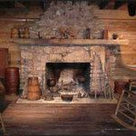 Working hearth inside log cabin replica exhibit.
